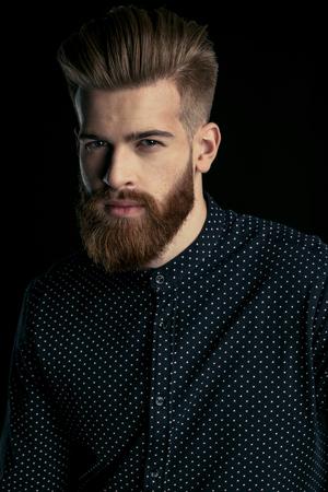 knappe bebaarde man in een stijlvol shirt camera kijken