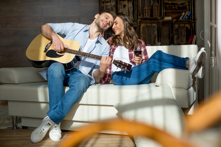 young couple resting together on sofa with acoustic guitar and red wine