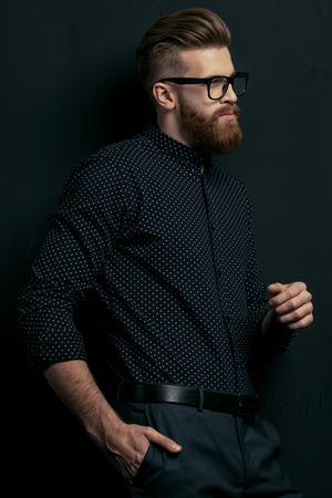 bebaarde jonge stijlvolle man in brillen poseren op zwart