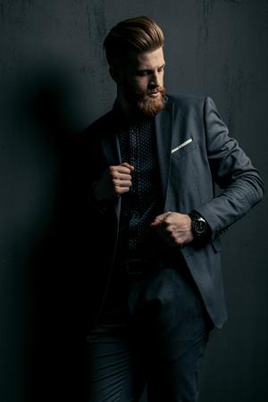 knappe bebaarde man in trendy pak die zich voordeed op zwart