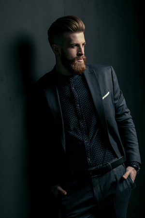 knappe bebaarde man in trendy pak staande met de handen in de zakken op zwart