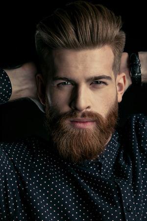 bebaarde man hipster met handen achter hoofd camera kijken