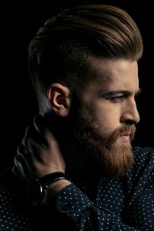 portret van knappe stijlvolle bebaarde man met de hand op de nek