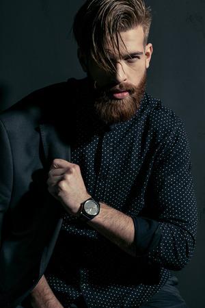 knappe bebaarde man hipster met jas op schouder camera kijken