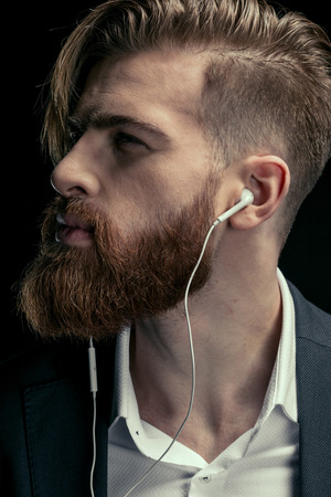 stijlvolle man luisteren muziek met oortelefoons op zwart