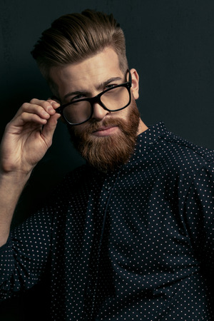 bearded young man hipster adjusting eyeglasses and looking at camera
