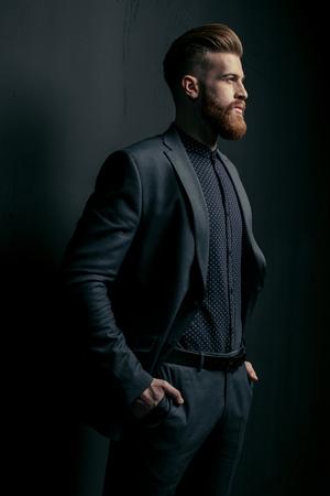 knappe bebaarde man in trendy pak wegkijken op zwart