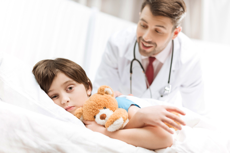 child patient lying in bed with smiling doctor behind Stock Photo