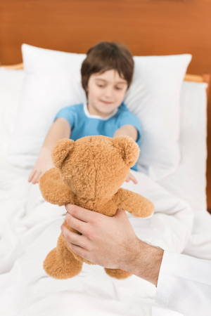 doctor showing child patient in bed