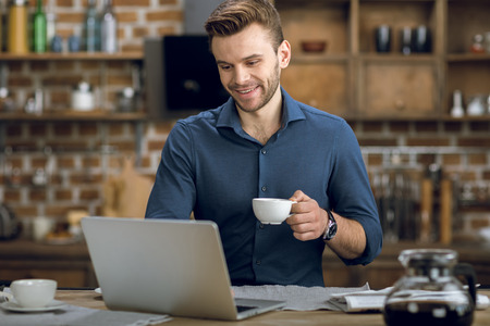 young man using laptop while drinking coffee at home