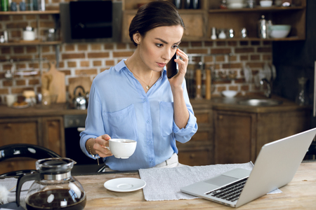 businesswoman with coffee cup using laptop and talking on smartphone