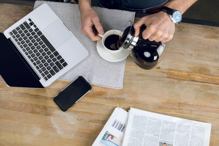 homeoffice: man pouring coffee in cup on desk with laptop and newspapers Stock Photo