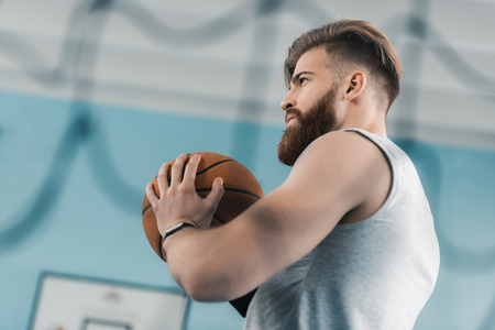 concentrated young basketball player holding ball