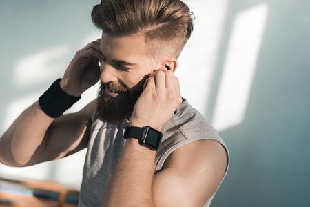 lachende sportieve man luisteren naar muziek in de sportschool