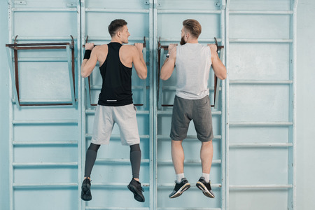 Sportieve mannen die op sportuitrusting in de sportschool uitoefenen
