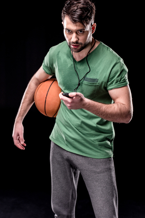 portrait of man with stopwatch and basketball ball looking away