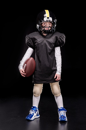 little boy american football player in uniform holding ball