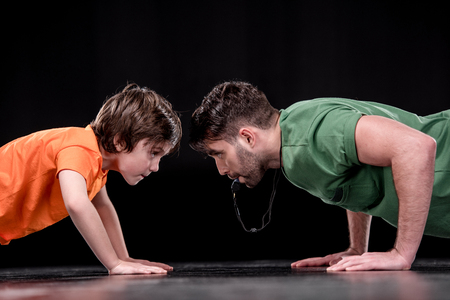 side view of man with whistle and boy doing push ups and looking at each other