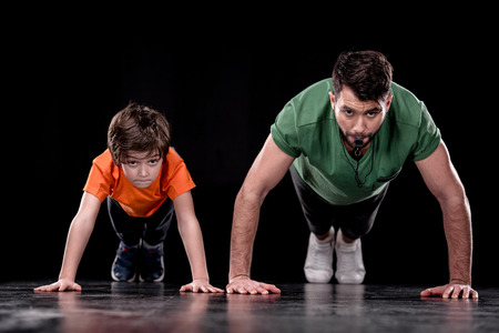 man and boy doing push ups together and looking to camera Stock Photo
