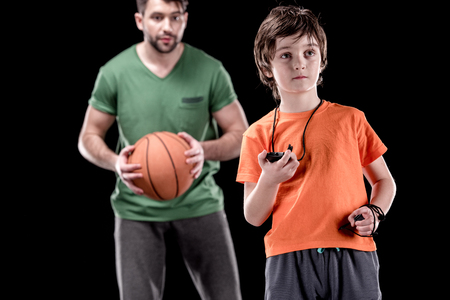 boy with stopwatch controlling time with man holding basketball ball on black