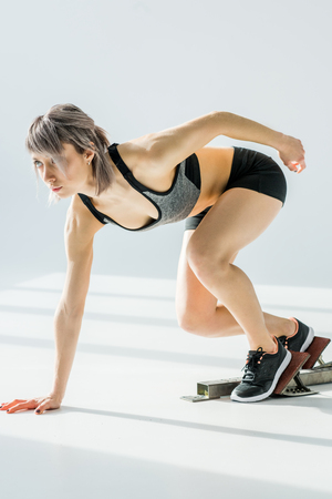 side view of sporty woman in starting position