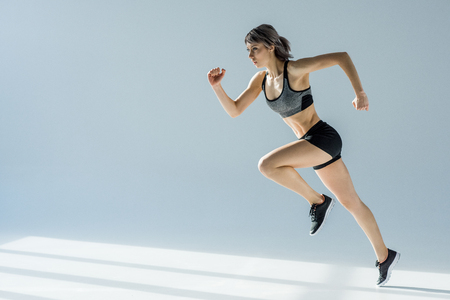 side view of running woman in sportive clothing Imagens