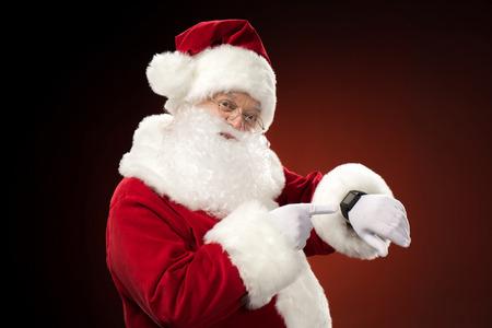 Weihnachtsmann, der auf intelligente Uhr zeigt Standard-Bild