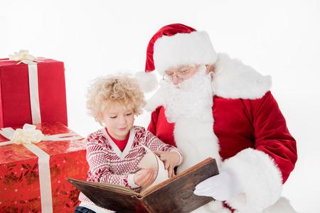 Santa Claus and kid reading book together Standard-Bild