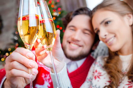 christmastime: Couple toasting with champagne glasses