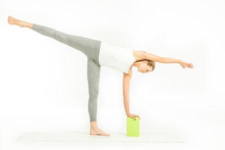 chandrasana: Sportswoman exercising with yoga block