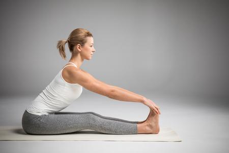 Vrouw zit in yoga positie
