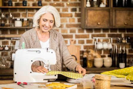 Woman using sewing machine Stock Photo
