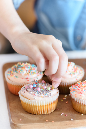 girls hand decorating cupcakes with confetti