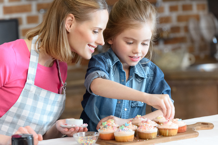 daughter and mother decorating cupcakes with confetti Banco de Imagens