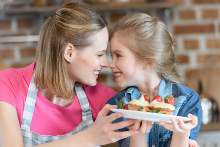 mother and daughter holding homemade cupcakes with strawberries
