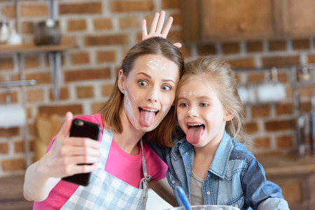顔をしかめる母と娘の家庭で調理しながら selfie を作る