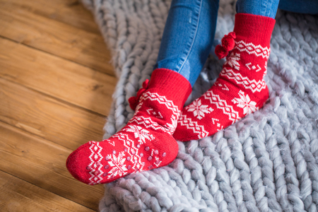 Female feet in cute red and white socks on knitted blanket