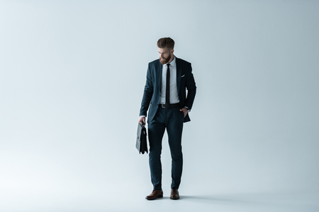 bearded businessman with hand in pocket holding briefcase