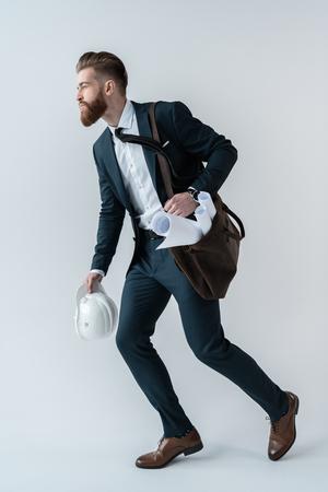 hombres corriendo: Hombre de negocios con sombrero duro y planos en bolsa de hombro corriendo