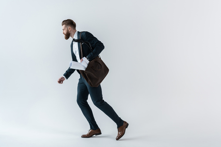 young businessman with blueprints in shoulder bag running on grey Stock Photo