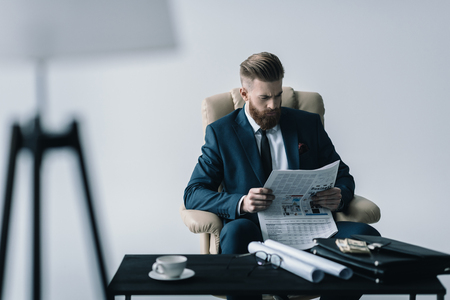 concentrated businessman reading newspaper in office