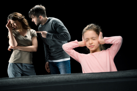 Little girl closing ears while parents quarreling,