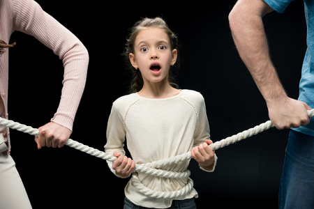 parents pulling over shocked daughter with rope, Stock Photo