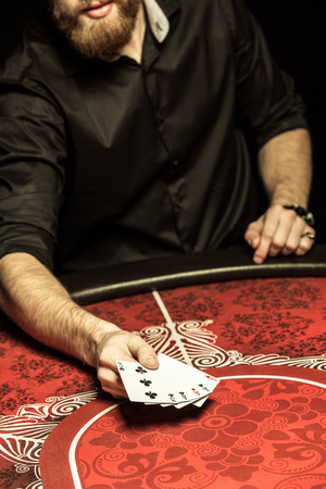 bearded man showing poker cards at table