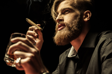 bearded man holding glass of whisky and smoking cigar on black