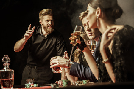 men and women playing poker in casino 스톡 콘텐츠