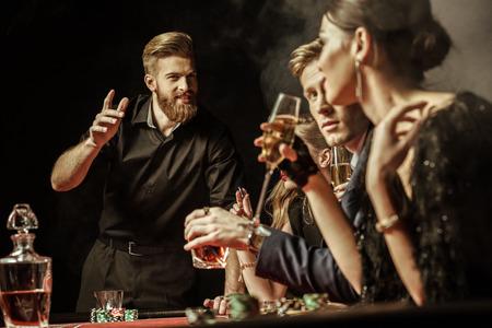 men and women playing poker in casino Archivio Fotografico