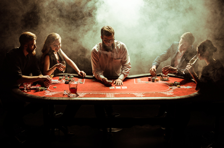 young men and women playing poker at table in smoke 스톡 콘텐츠