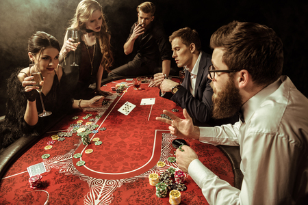 men and women with drinks playing poker in casino