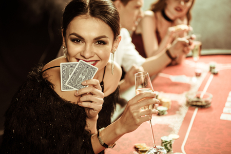 lachende vrouw met drankje en kaarten poker spelen